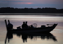 Silhouette Of Fishermen In Boat At Sunrise