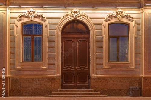 Two windows and door in a row on night illuminated facade of urban apartment building front view, St Poster