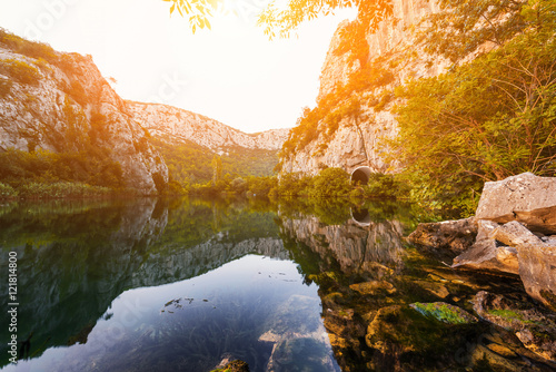 Foto auf Gartenposter Fluss Gentle sunset light at the canyon of river Cetina, surrounded by rocks and stones, nature landscape with reflection in a water, Omis, Croatia
