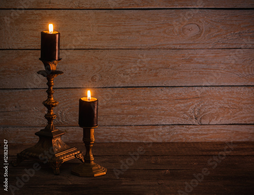Foto op Plexiglas Wand burning candles in vintage candlestick on wooden background