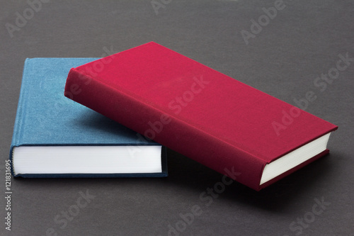 blue and red hard covered books face up and closed on a gray