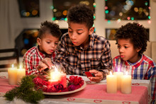 Mulatto Kids Lighting Christmas Candles. Boys Light Candles With Matches. Decorating Christmas Table At Night. Few Hours Before Holiday.
