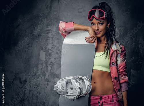 Fotografie, Obraz  A woman posing with a snowboard on grey background.