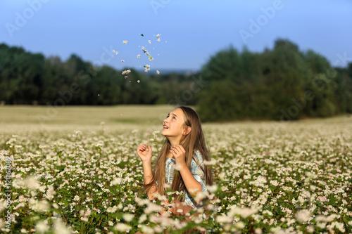 Fototapeta Piękna dziewczynka podrzuca kwiaty na łące. obraz