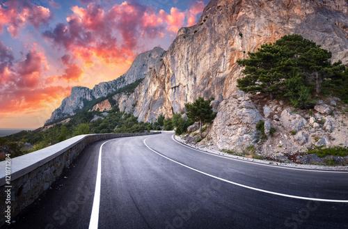 droga-asfaltowa-kolorowy-krajobraz-z-piekna-wijaca-halna-droga-z-perfect-asfaltem-z-wysokimi-skalami-zadziwiajacy-niebo-przy-zmierzchem-w-lecie-panoramiczny-tlo-podrozy-autostrada-w-gorach