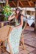 Beautiful brunette woman in long dress and hat relaxing in beach restaraunt