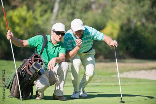 Plakat Golf. Golfista i caddy kontemplując oddanie strzału