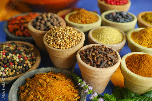 Poster Maroc Collection of different spices in old clay bowls in colorful oriental style