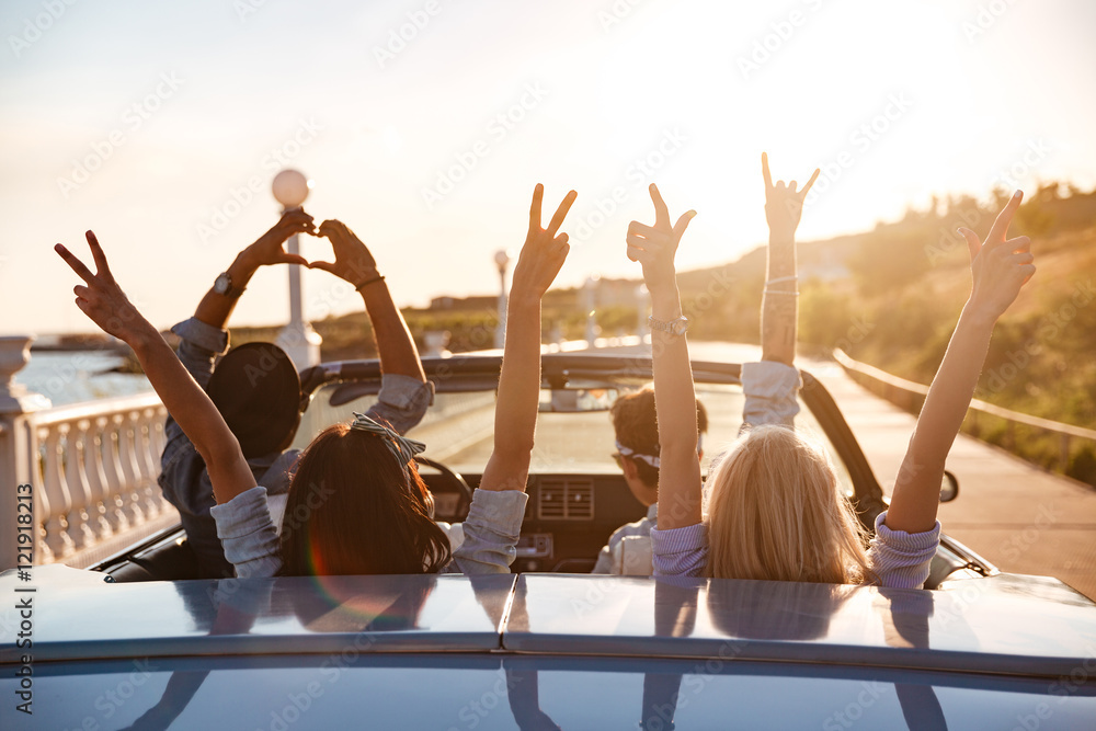 Fototapeta Happy friends in cabriolet with raised hands driving on sunset