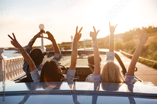 Happy friends in cabriolet with raised hands driving on sunset Fototapet