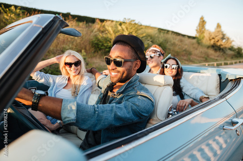 Cheerful young friends driving car and smiling in summer