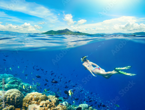 Woman swims around a coral reef surrounded by a multitude of fish on the background Islands..North Sulawesi, Indonesia.