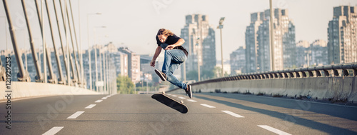 Skater doing tricks and jumping on the street highway bridge, through urban traffic. Free riding skateboard. Panorama view