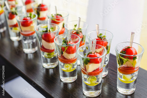 Poster Entree Catering for party. Close up of appetizers with cherry tomatoes, green olives, olive oil, cheese and spices in short glasses on wood brown table. Horizontal color image.