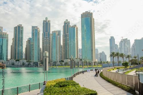 Fotografie, Obraz  People walking along the waterfront promenade that runs along the Burj Khalifa Lake and the Burj Khalifa