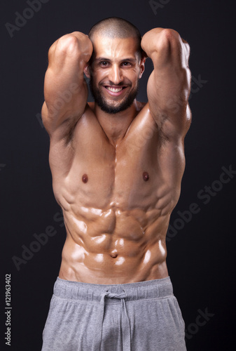 Smiling fit man flexing the abdominal on black background