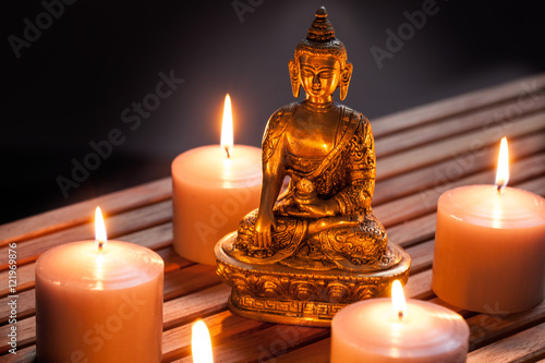 Bronze Buddha with warm lighted candles over wooden background Fototapeta