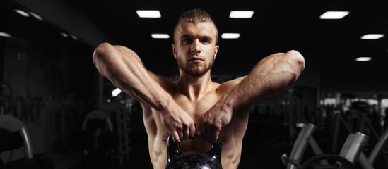Fototapeta na wymiar Fitness man doing a weight training by lifting heavy kettlebell
