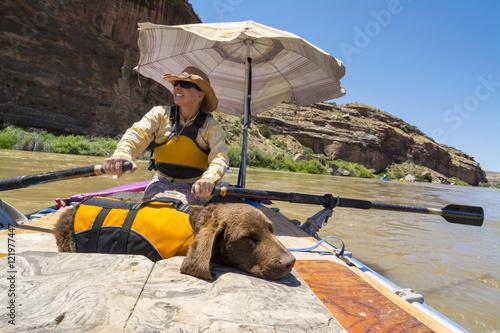 A woman and her dog rafting the Colorado River, Fruita, Colorado.