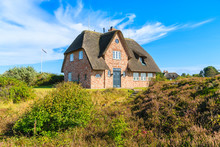 Traditional Red Brick House With Thatched Roof On Meadow Near Wenningsted Village On Sylt Island, Germany