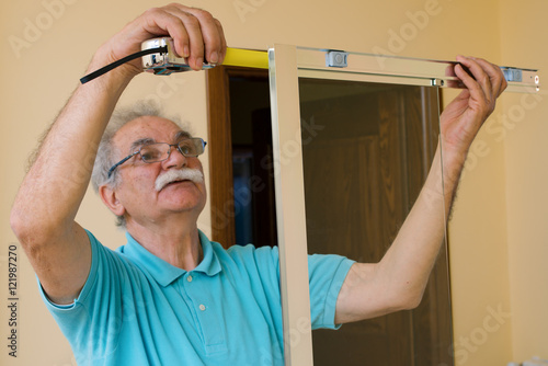 senior man installing and measuring a shower box, do-it-yourself ...