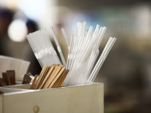 Plastic Transparent Straws, Wooden Sticks For Coffee And Drinks, And Sugar Over Blurred Background
