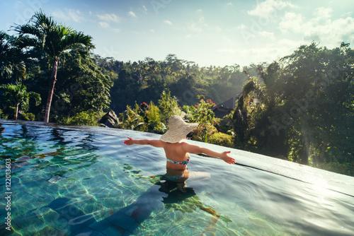 Foto op Aluminium Bali sexy woman enjoying the sun at infinity summer swimming pool at luxurious resort
