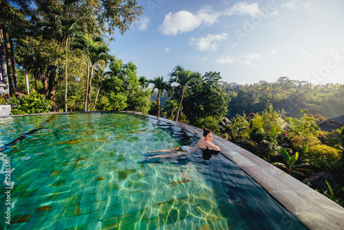 portrait of beautiful woman in luxurious resort. Young girl taking a bath and relaxing at infinity swimming pool