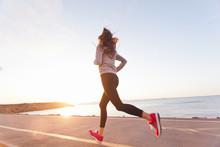 Young Woman Athlete Running At Sunset On Seashore Sidewalk. Girl Runner Training On A Beach