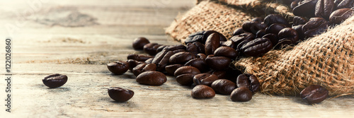 Foto op Canvas Koffiebonen Roasted coffee beans on old wood background