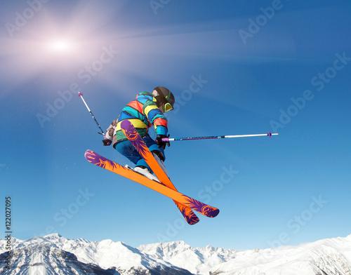 Fotografía  Skifahrer springt vor blauem Himmel und Sonne