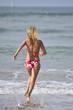 Back view of woman in bikini running into the water
