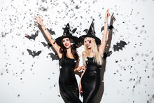 Two Happy Women In Black Witch Halloween Costumes On Party