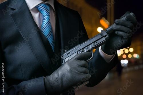 Fototapeta  Hitman or assassin holds pistol with silencer in hands.