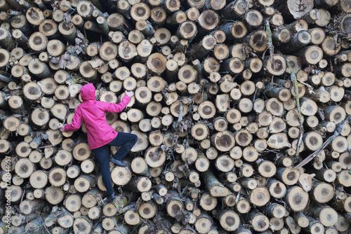 Valokuva  grimpeuse escaladant une pile de troncs