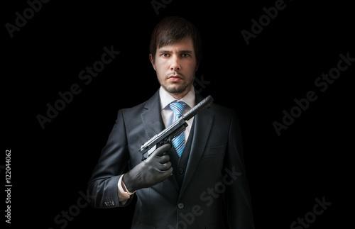 Obraz na plátně  Hitman or murderer with pistol with silencer on black background