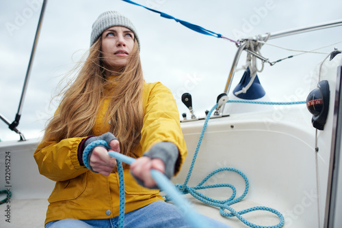 Fotomural Young strong woman sailing the boat