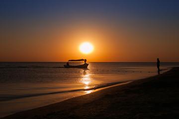 Silhouettes of boats and man at sunset