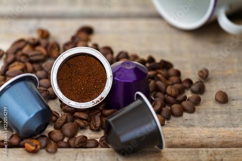 Fotografia  Italian espresso coffee capsules or coffee pods on wood background with some roa