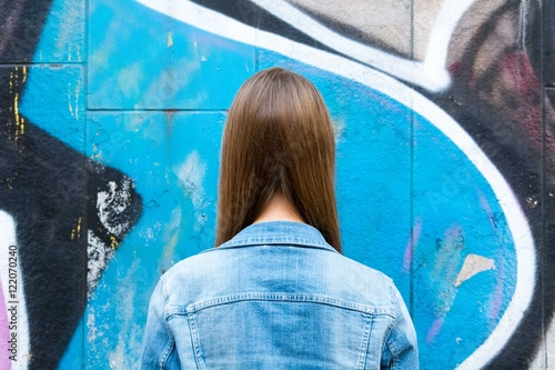 Tuinposter Graffiti Rear View Of Woman Against Wall With Graffiti