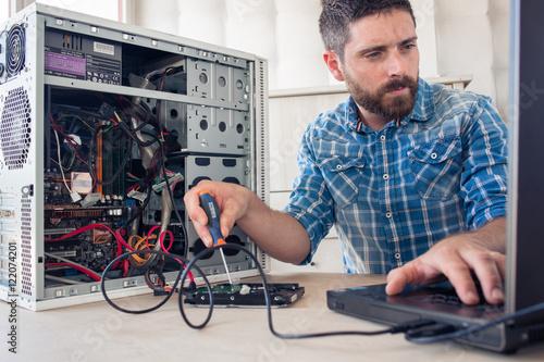 Engineer repairs computer's hard drive
