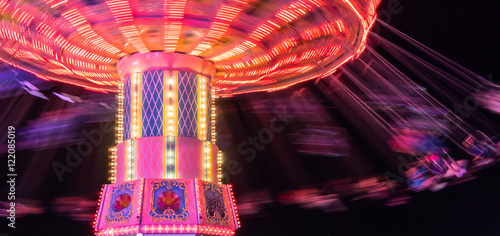 Photo  people  spinning around fast and high in swings at the brightly lit ride at the
