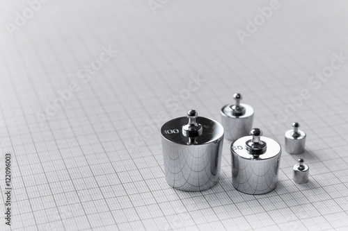 Metallic weights on background of millimetre paper