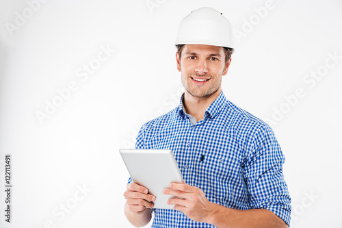 Fotografia  Cheerful man architect in hard hat standing and using tablet