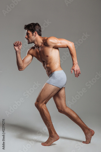 Portrait of a confident naked athletic man in underwear posing