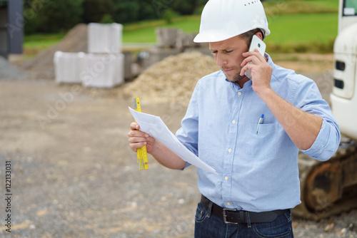 Fotografie, Obraz  architekt auf der baustelle telefoniert mit ernstem gesicht