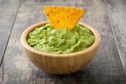 Fotografía  Guacamole in a bowl and nachos on wooden background