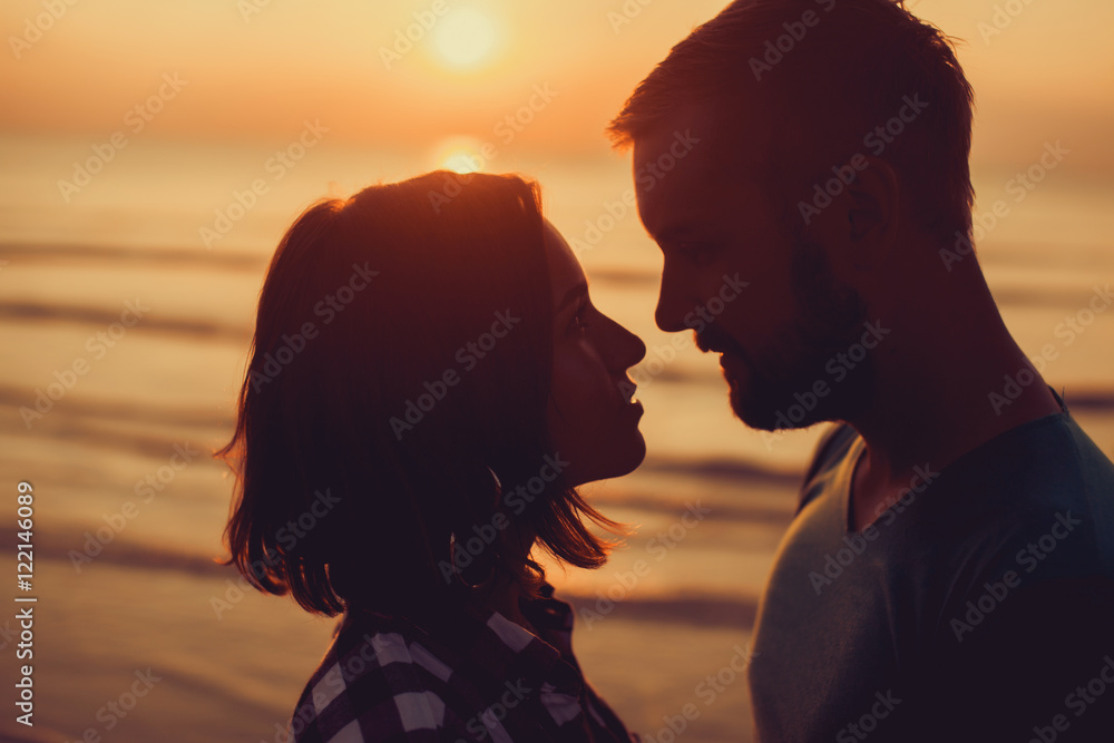 Fototapeta silhouette of couple on sunset beach, beautiful background about love and relationships, man and woman