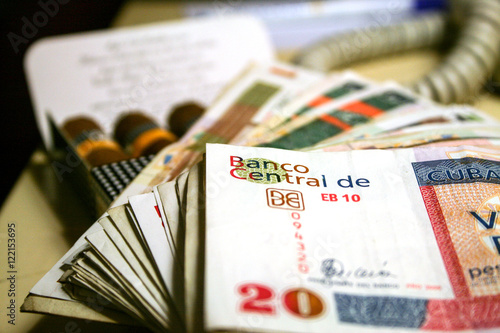 Photo  Cuban convertible pesos, with some blurred cigars in the background