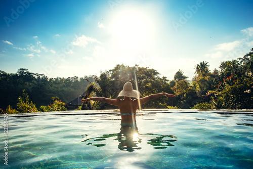Foto op Aluminium Bali Infinity pool at luxurious exotic island. Portrait of girl wearing hat enjoying the sun at pool